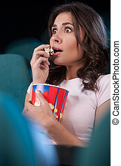 Women at cinema. Beautiful young women eating popcorn while watching movie at the cinema