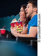 Couple watching horror movie. Side view of terrified people in watching movie at the cinema