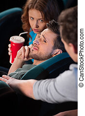Talking at phone in cinema. Young men talking at phone while watching movie at the cinema