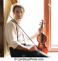 Musician and the violin. Handsome young man sitting on the...