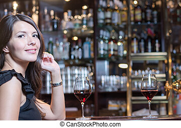 Beautiful woman seated at a bar counter - Beautiful young...