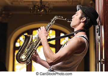 Playing funky music Handsome young jazz man playing sax with...