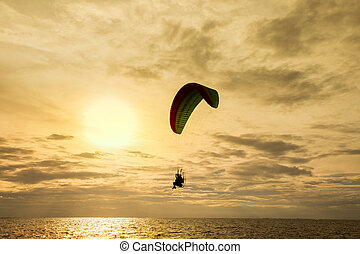 Silhouette of paraglider at sunset