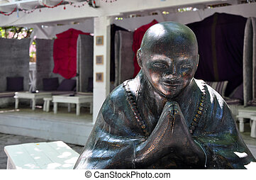 interior of open air restaurant with big Buddha bronze...