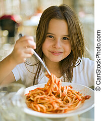 child having spaghetti - young girl eating spaghetti in...