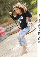 up and down - little girl on a swing with motion blure
