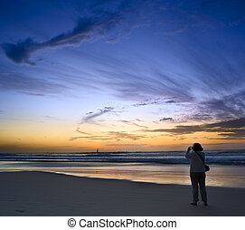 shooting the sunset - a tourist taking picture of the sunset...