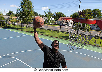 Man Dunking a Basketball - A young basketball player dunking...