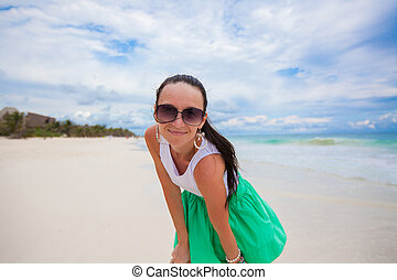 Close-up of young woman on the white exotic beach looking at...