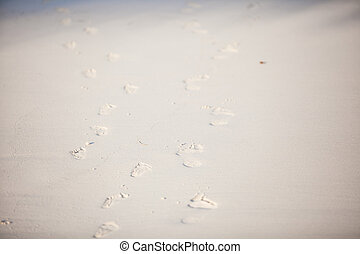 Human footprints on the white sandy beach