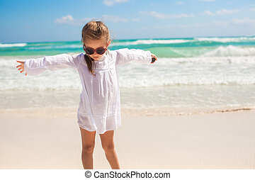 Adorable little girl having fun on an exotic white beach at...