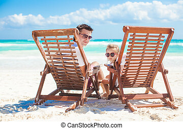 Little cute girl with her young dad sitting on beach wooden chairs looking at camera