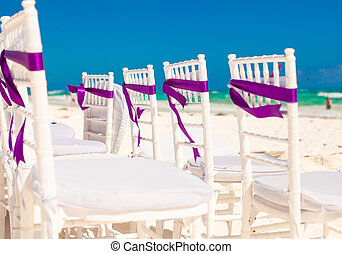 White wedding chairs decorated with purple bows on sandy...