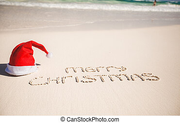 Santa Hat on white sandy beach and Merry Christmas written...