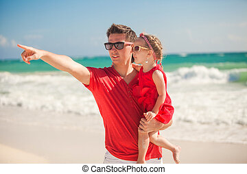 Young father with little girl on tropical beach