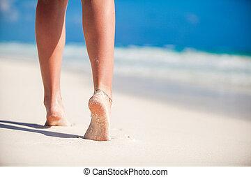 Women's beautiful smooth legs on white sand beach