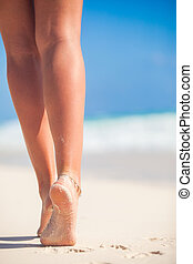 Women's beautiful smooth legs on white sand beach