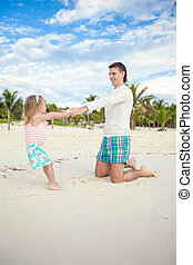 Little cute girl and her young father having fun at white beach