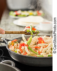 Female cooking vegetables and chicken in pan