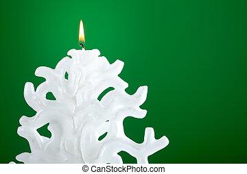 Christmas candle shaped like a Christmas tree on green...