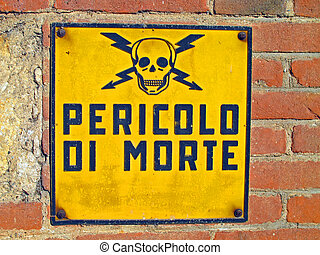 Danger of death signs with skull and crossbones written in Italian and brick wall
