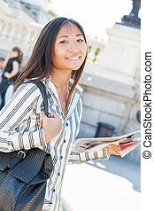 Pretty asian tourist holding a map - Beautiful asian tourist...