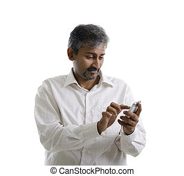 Indian male using mobile phone to online / texting / sms ,...