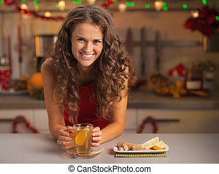 Smiling young woman drinking ginger tea in christmas...