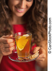 Closeup on ginger tea with lemon in hand of young woman
