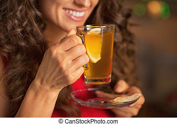 Closeup on happy young woman drinking ginger tea with lemon