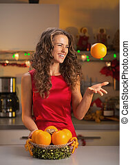 Happy young woman throwing up orange in christmas decorated...