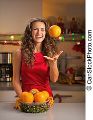 Smiling young woman throwing up orange in christmas...