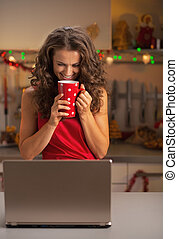 Happy young woman drinking cup of hot chocolate and looking on laptop