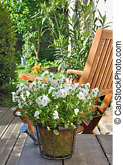 relaxation on terrace - viola pot on a terrace with a chair...