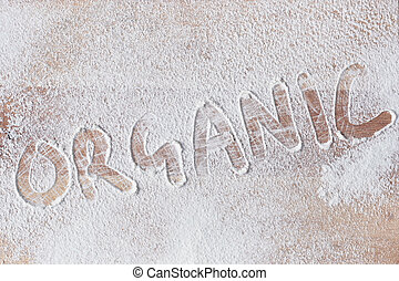 Organic written in flour on a wooden surface
