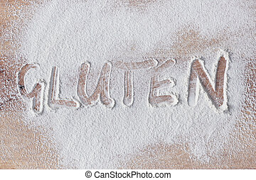 Gluten written in flour on a wooden surface