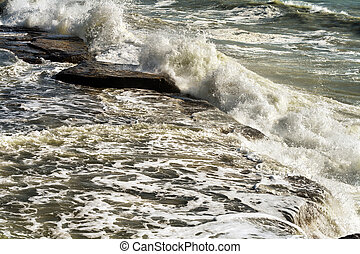 Sea waves beating against the rocks.