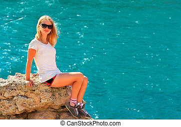 Young Woman relaxing on rocky cliff with blue Sea on background Summer Traveling and Healthy Lifestyle concept