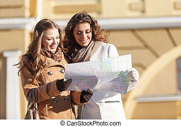 Friends looking at the map. Two beautiful young women...