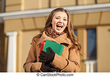 Happy student. Happy young women holding the books and...