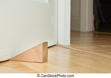 Door stopper - A wooden door stopper on a laminate floor