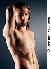good abs - Sexual muscular nude man posing over dark...