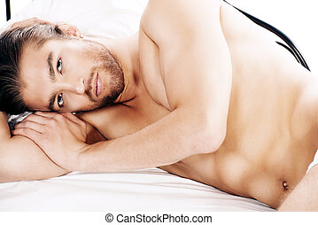 miss someone - Handsome nude man lying in a bed Isolated...