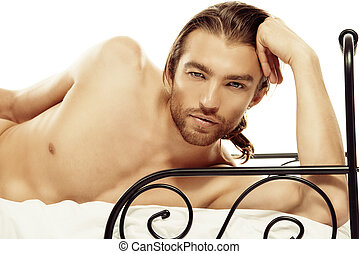 tempter - Handsome nude man lying in a bed Isolated over...