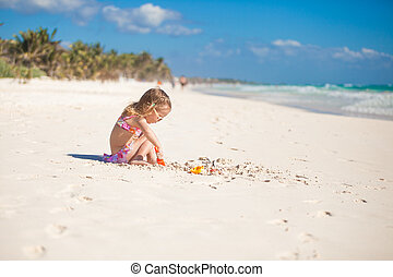 Adorable little girl in swimsuit playing at tropical...