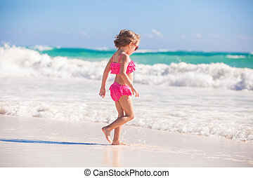 Little cute girl walking on the white sandy beach in Mexico