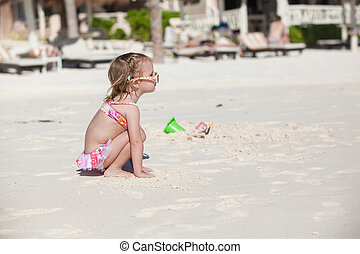 Adorable little girl in swimsuit at tropical carribean beach