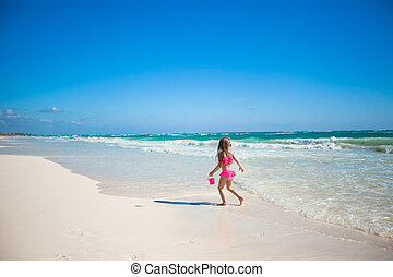 Adorable little girl in swimsuit having fun at tropical...