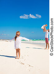 Little girl having fun with her cute sister and young father on white sand beach