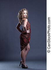 Coquettishly smiling curly girl posing in negligee -...